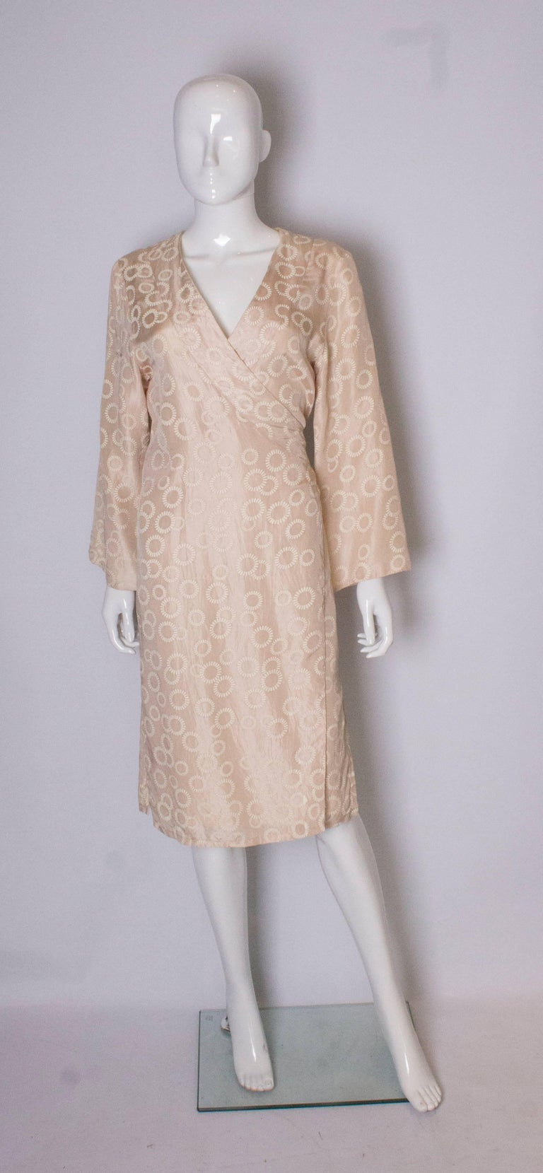 A silk wrapover, kimono style dress. The outer silk is a pale biscuit colour with a floral design, the lining is silk. The ties tie at the back. Bust up to 38/39'', length 45''.