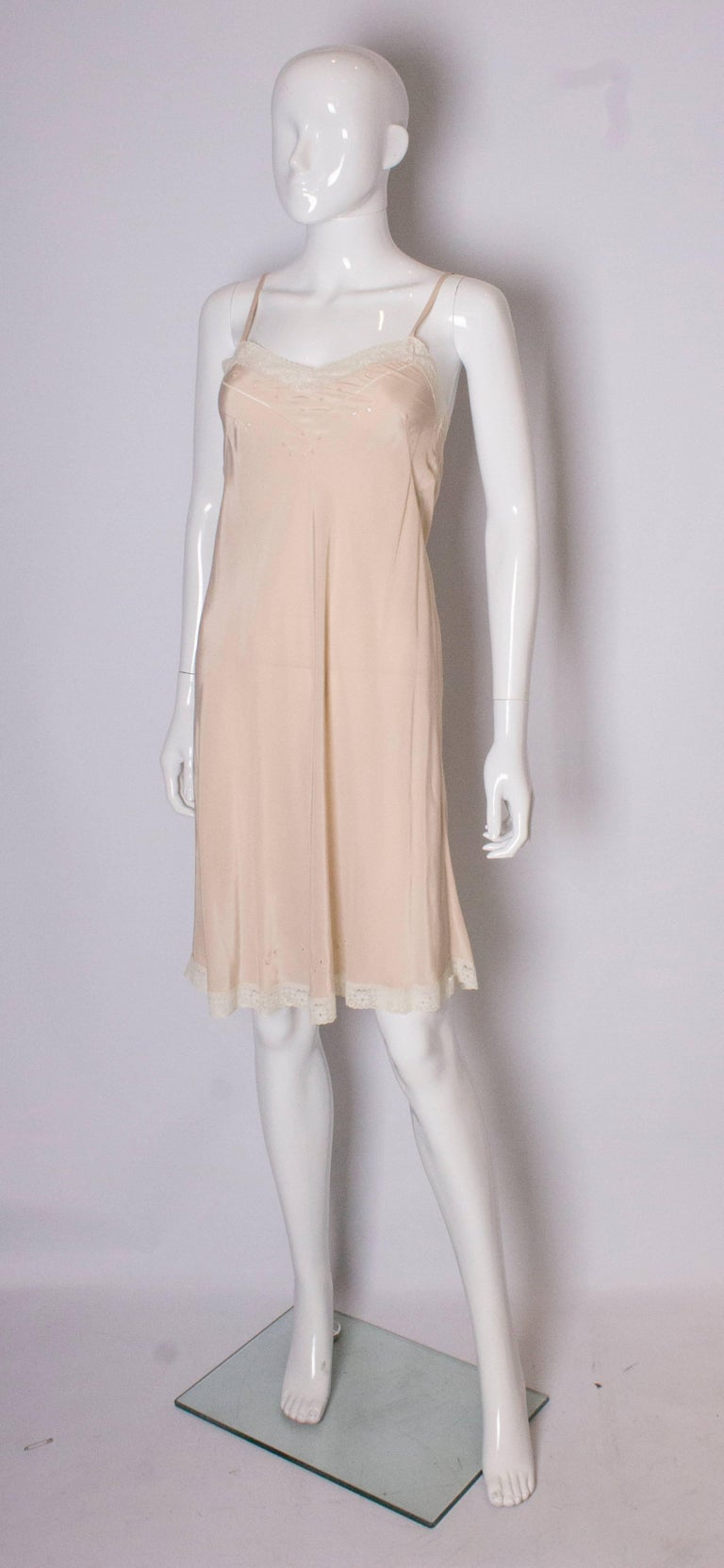 A lovely slip in a heavy silk, in a caramel colour with lace trim and stitch detail.