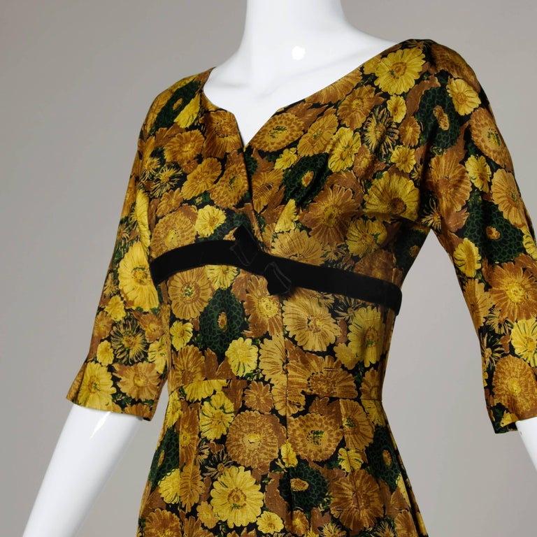 Elegant 1950s-1960s vintage floral printed silk cocktail dress with 3/4 length sleeves and hourglass silhouette. Fully lined with back metal zip and hook closure. Fits like a modern size small. The measurements are as follows: Bust: 36