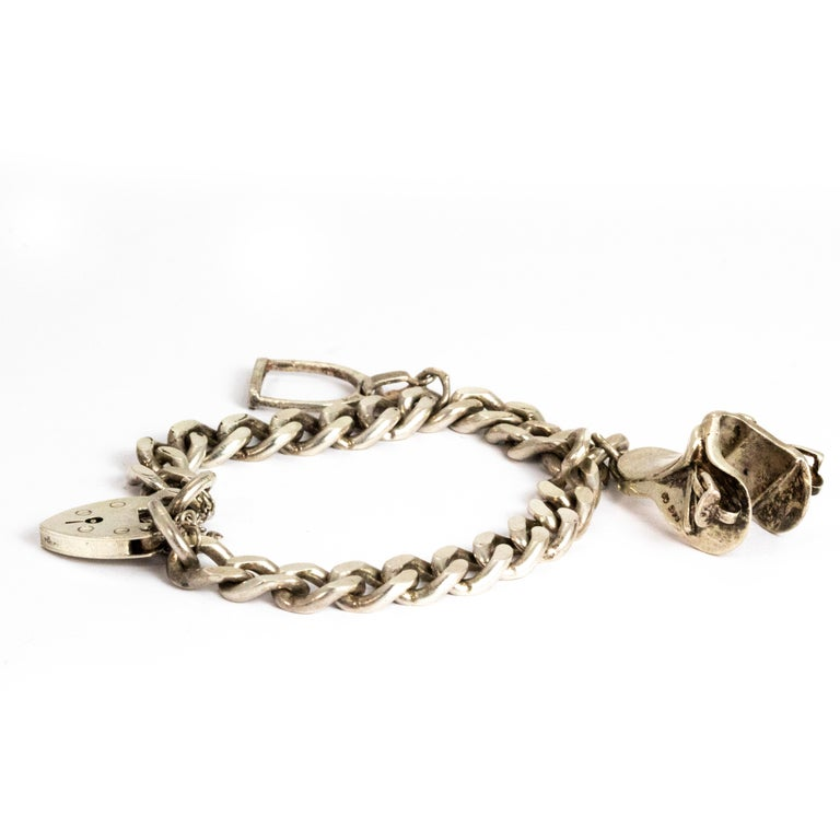 This chunky and fun equestrian themed charm bracelet it modelled out of silver and is very heavy in weight and chunky in style. The bracelet comes with two silver charms, one being a saddle and the other is a stirrup. The fastening on this piece is