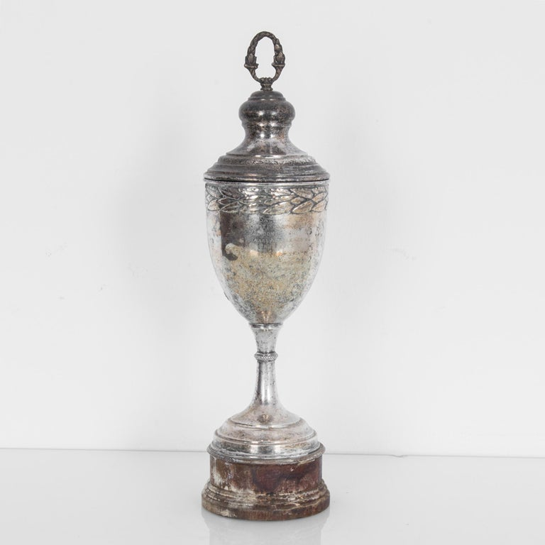A silver plated trophy from Europe, made circa 1900-1930. A slender silver cup topped with a victory wreath, girdled with a circle of laurel leaves. The tarnishing of the silver obscures the words engraved into the surface, lending the trophy a