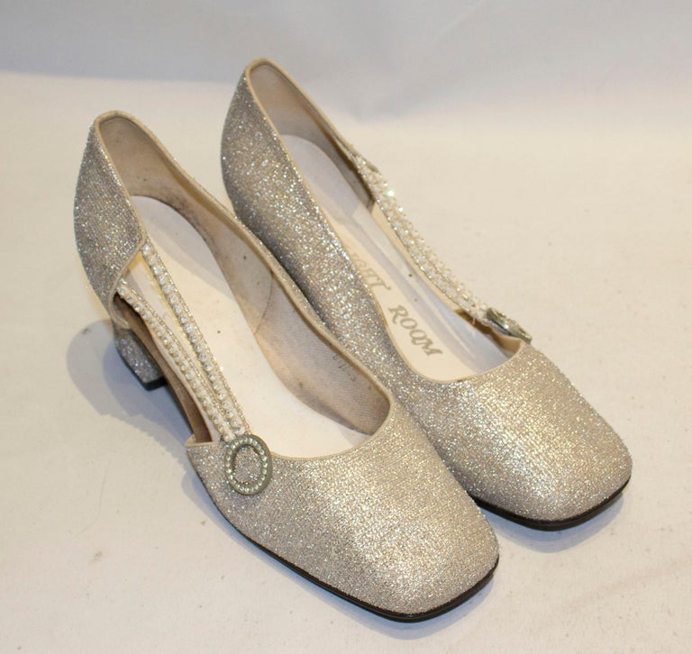 A fun pair of silver shoes by Starlight Room. The shoes have a 3'' heel, and two diamante strips along one side.  Size 8 1/2 B.