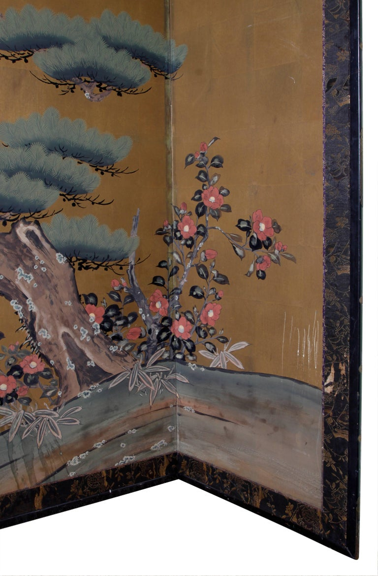 Vintage six-panel Asian screen with gold leaf decoration. Scenic rendering of a sculpted tree, flowers and a river.