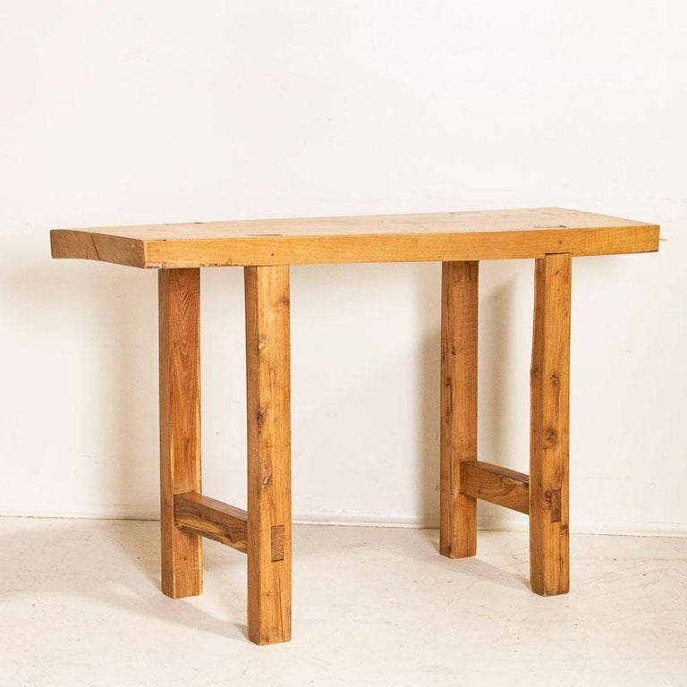 It is the raw, natural wood top that one finds intriguing in this rustic console table. It originally served as a work table, resulting in the appealing worn patina of the wood top due to the deep gouges, scrapes, stains and old cracks. The square