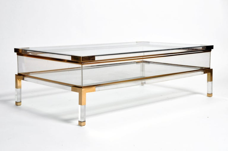 This sleek vitrine table has a glass top that slides opens to reveal a storage space below. Walled with Lucite, the clear glass bottom shelf allows the chrome frame to show through; the effect is airy and angular. This versatile display case is a