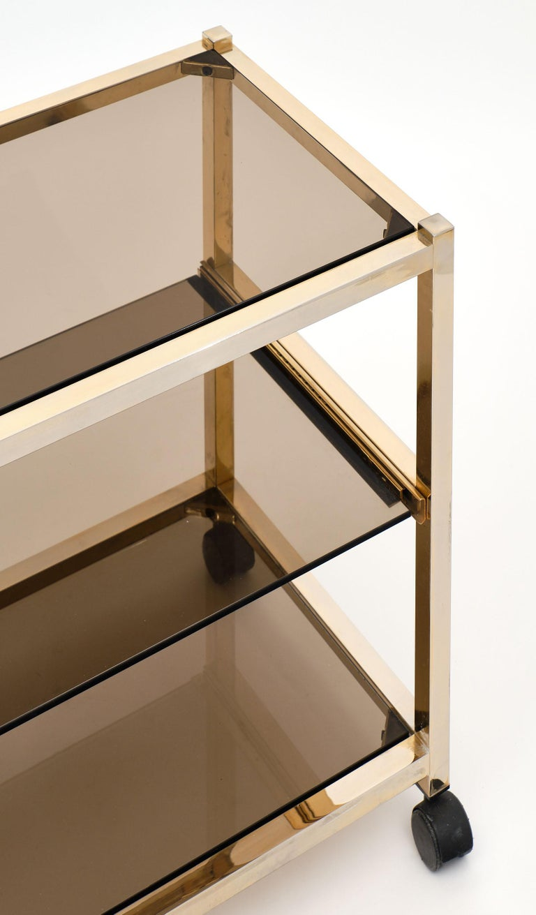 Vintage smoked glass side table on original casters and featuring a sliding middle glass shelf. We love this brass piece with both function and excellent modernist aesthetics.