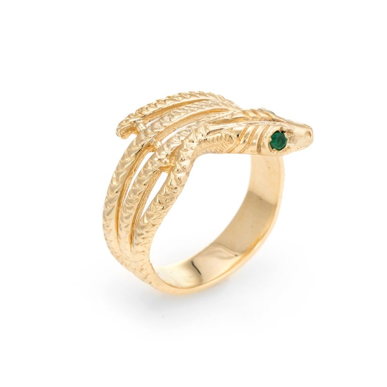 Finely detailed vintage snake ring, crafted in 18 karat yellow gold.   Two estimated 0.01 carat emeralds adorn the snakes eyes (total estimated weight of 0.02 carats).        For centuries the snake has represented eternal love and faithfulness. The