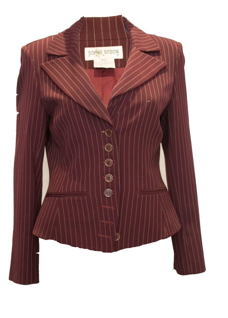 A fun vintage jacket by Sophie Sitbon. The jacket has a burgundy background ,with white stripes in single and double lines. It  has a front button opening,with two pockets at hip leval and interesting flared sleaves.
