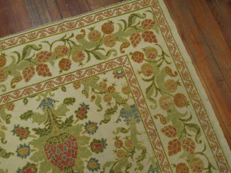 A room size Spanish rug. Ivory field, accents in green, blue, raspberry and orange.