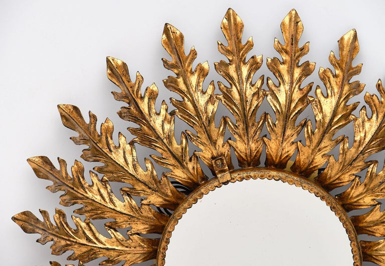 Spanish vintage sunburst mirror with backlight featuring gold leafed embossed tole rays adorning a circular central mirror. The backlight gives this piece a beautiful glow. It has been newly wired to fit US standards.