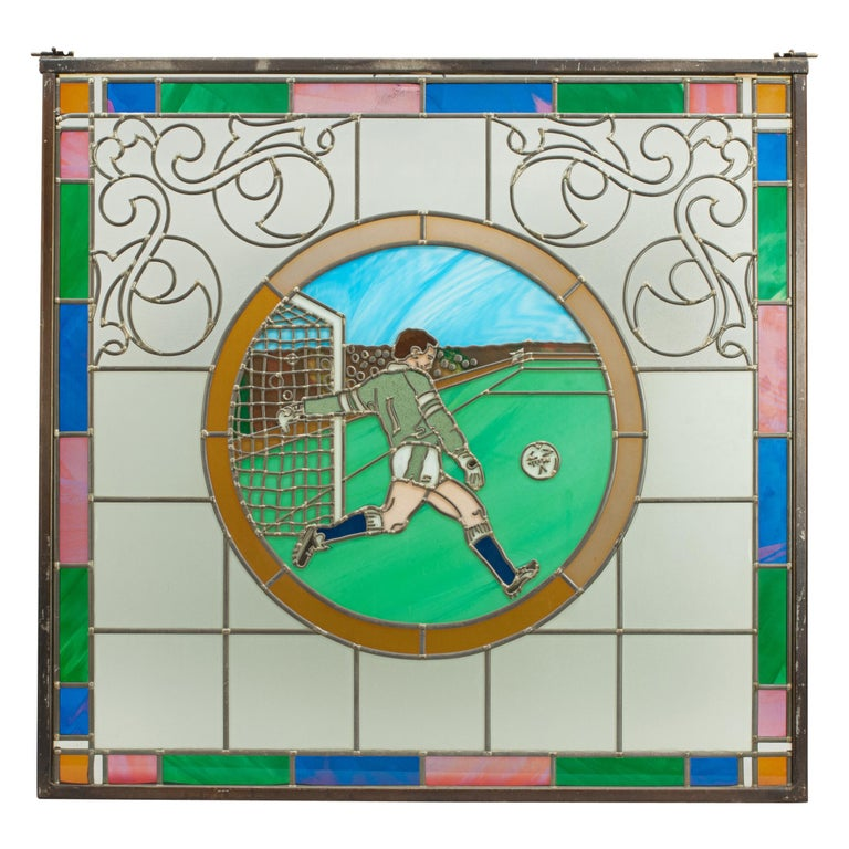A magnificent set of four sporting stained glass windows depicting scenes of football, golf, fishing and athletics. The stained glass football window shows a goalie just about to kick the ball, the golf window shows a male golfer hitting out of a