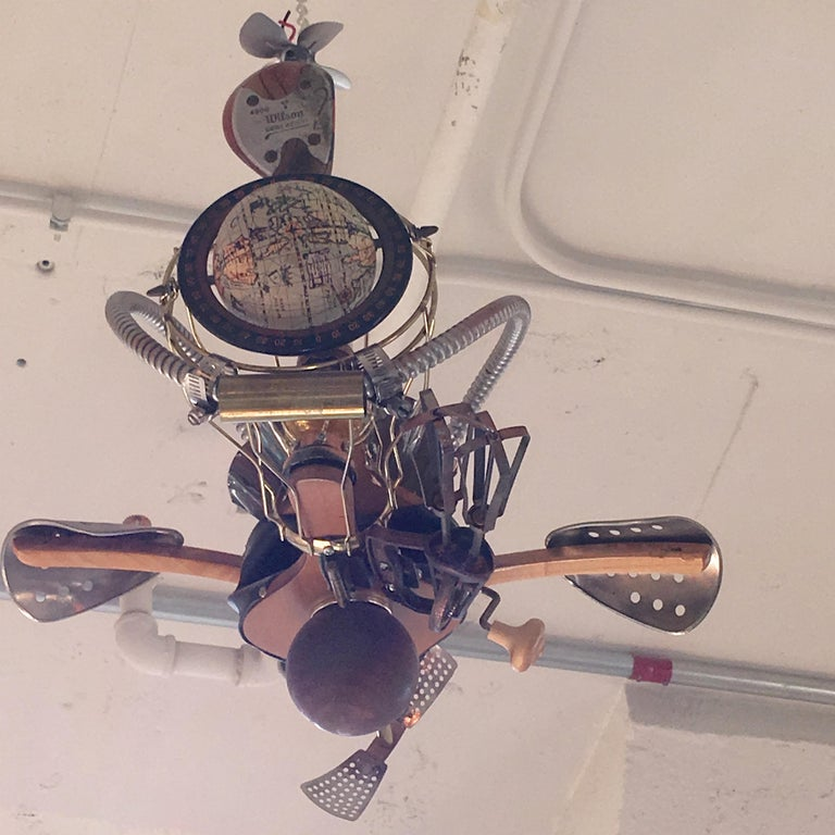Humorous Steampunk Kinetic sculpture of a fantasy flying machine in the spirit of Chitty Chitty Bang Bang and Wild Wild West, creatively and artistically assembled from found items including: old fashioned manual egg beater, fireplace bellows,