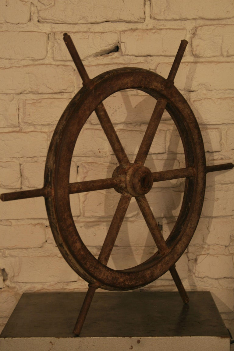 The original antique steering wheel from a fishing boat or a ship. Steel structure, profiled wood inside the wheel frame, rims screwed with bolts. Preserved remains of the original paint, the whole covered with a beautiful patina of