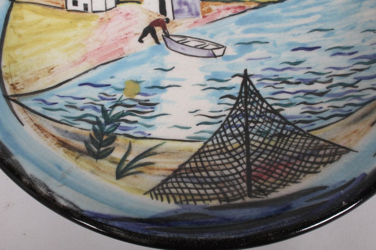 Artist Nicolai Cikovsky (1894-1984) Russian/American, hand painted ceramic charger for Stonelain, circa 1950s, part of the (AAA) or Associated American Artists Gallery, NYC. Polychrome glaze decoration depicting an East Coast coastal scene with