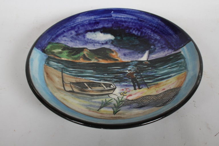 Artist Nicolai Cikovsky (1894-1984) Russian/American, hand painted ceramic charger for Stonelain circa 1940s, part of the (AAA) or Associated American Artists Gallery NYC. Polychrome glaze decoration depicting a East Coast coastal scene with