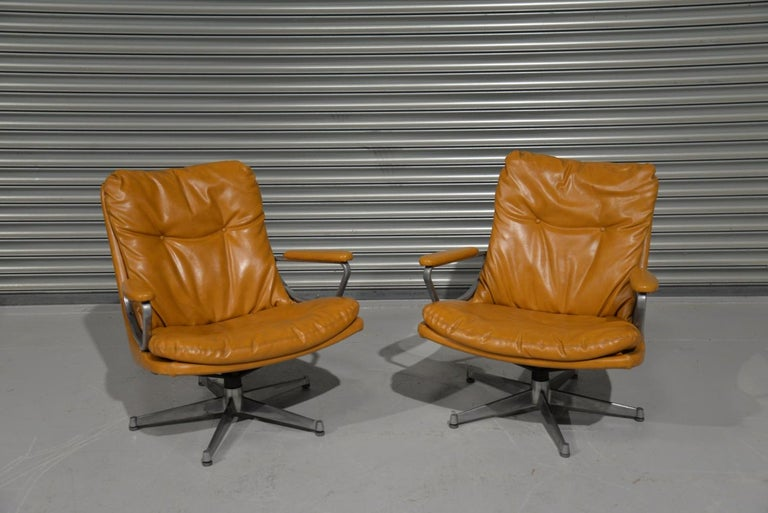 Discounted airfreight for our US and International customers (from 2 weeks door to door).  The sister chair to the King chair by Strässle and designed by Andre Vandenbeuck of Belgium. The swivel lounge armchairs are upholstered in beautiful soft tan