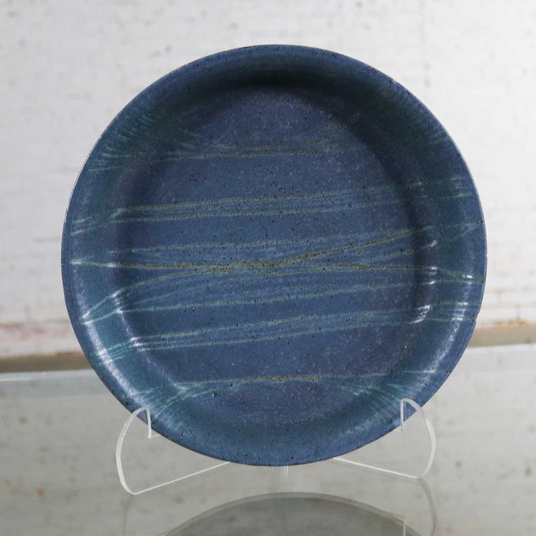 Handsome piece of studio stoneware pottery by Kansas artist Jack E. Wright. This round charcoal gray plate has silver and gold geometric lines in the mat glaze of the plate. It is in wonderful vintage condition. It does have a small nick like
