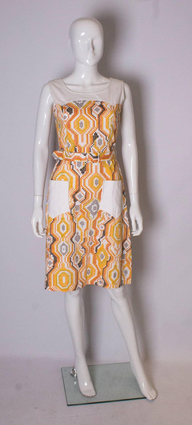 A great summwer dress by D L Barron. it is in a fun print of white, yellow and brown, with two large white pockets.