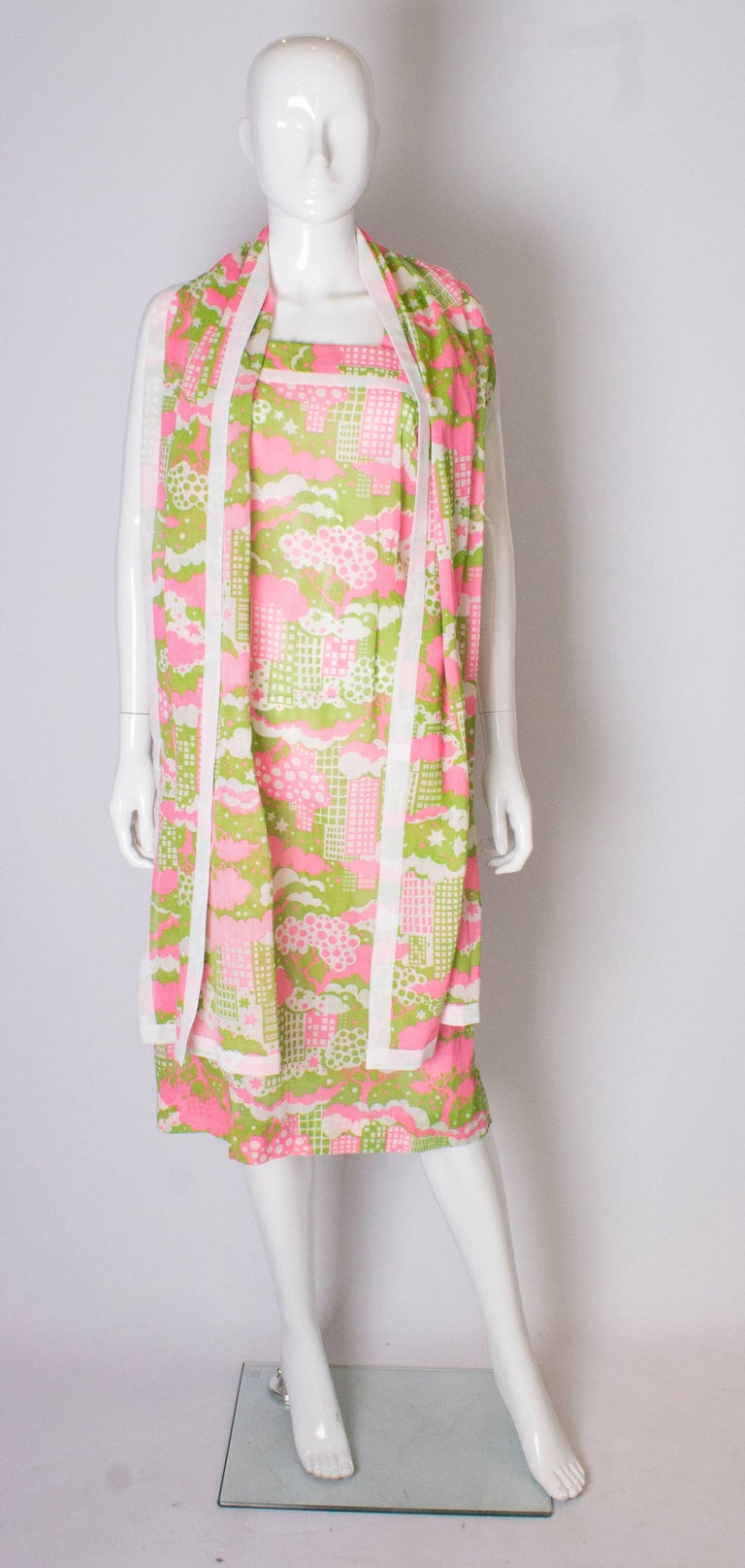 A fun abstract printed  sundress with matching scarf. The dress is a print of pink, white and sage green ,  with a white trim.  It has two straps and a central back zip. The scarf is the same fabric and measures 88'' x 18''.