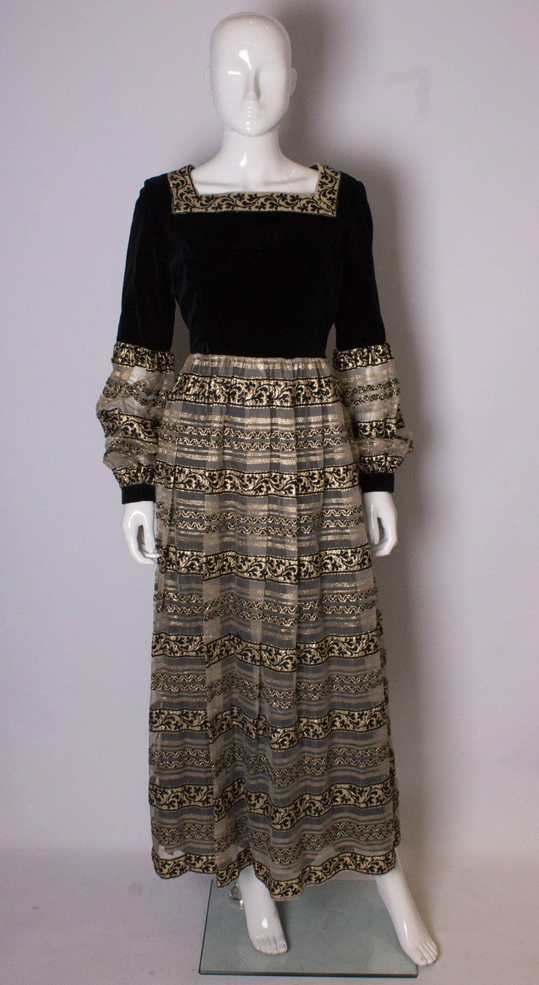 A chic vintage gown by Susan Small.  The dress has a black velvet upper body and upper sleeves, with a gold and black skirt and lower sleeves.