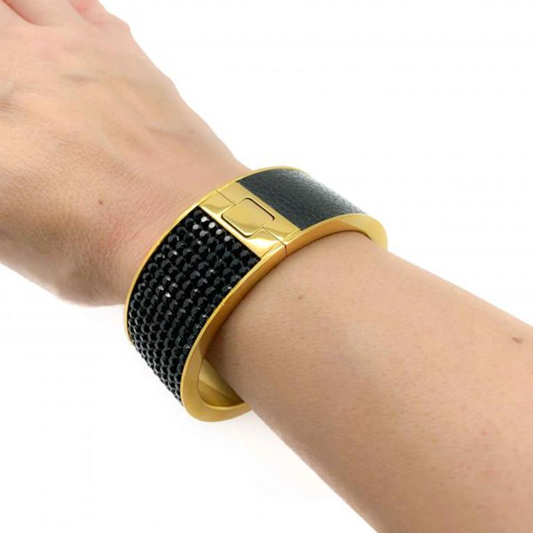 A substantial and super stylish Gold and Black Vintage Swarovski Bangle. One of the best examples of a Swarovski cuff. Bold and beautiful. Featuring stunning pave set black crystals on one half and leather on the other upon a high quality gold