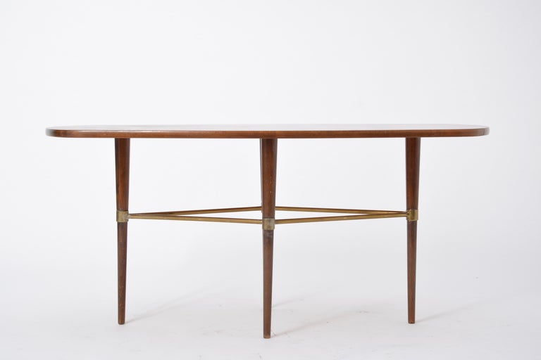 Swedish Mid-Century Modern coffee table by Förenades Möbler  This coffee table was produced by the Swedish company Förenade Möbler in the 1950s. The table top features beautiful wood veneer, and the legs a wood structure with brass detailing. The