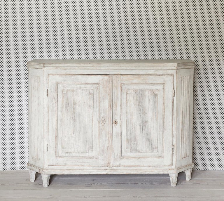 Beautiful Swedish white painted wooden Gustavian cabinet with two doors and grooved panels from late 19th century.