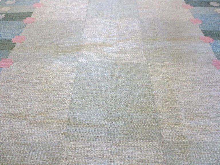 This is beautiful vintage Swedish Kilim rug by designer Anna Joanna Angstrom from the mid-20th century. Its soft colors of greens, blues, and pinks evoke a sense of calmness while the rug's vertical and horizontal elements create a mirrored affect