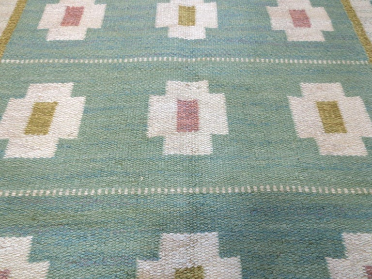 This is a vintage Swedish Kilim signed by artist Anna Greta Sjoqvist from the mid-20th century. It features calming tones of greens, greys, ivories, rosy pinks, and yellows in repeating geometric motifs that runs within the borders and set against
