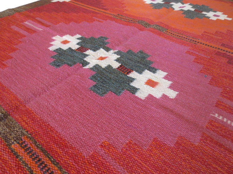 This a lovely vintage Swedish rug signed by designer Ingegerd Silow from the mid-20th century. The rug features jewel tones of ruby, orange, and fuchsia bordered by browns and geometric diamonds which serve to frame the main design of the rug. The
