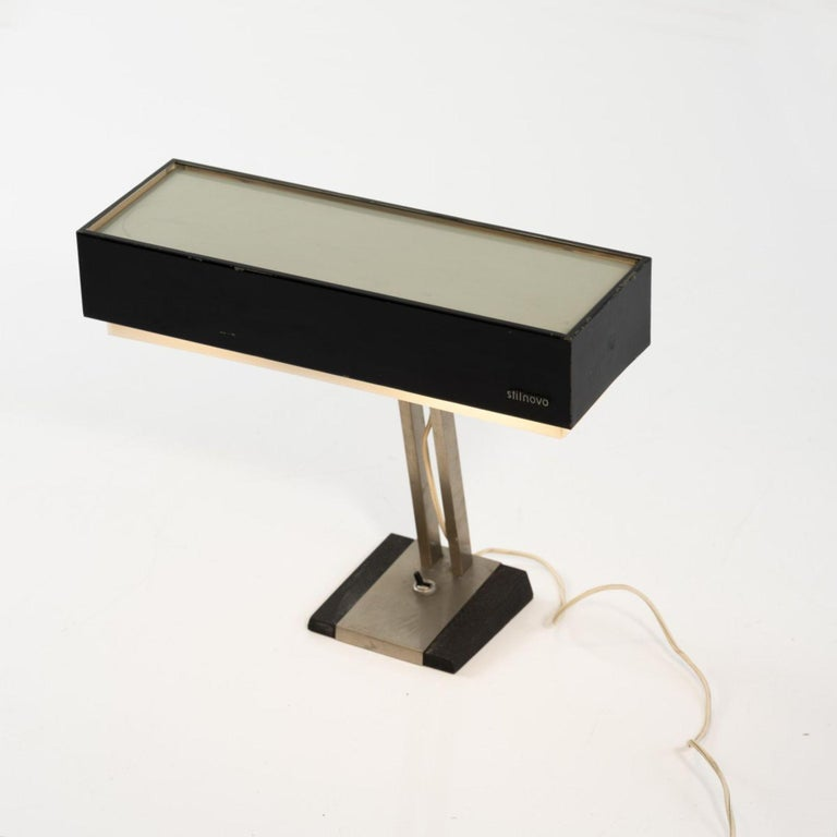 Stilnovo table light is an original decorative object realized in the 1960s by the Italian Factory Stilnovo, Milan.  Made and created by Stilnovo.   Marked: Stilnovo.  Main materials: metal tube, sheet metal, painted black and grey, acrylic