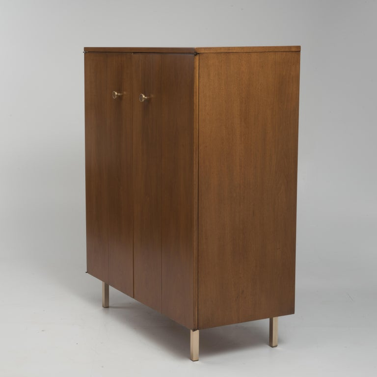 An elegant midcentury men's tall dresser by Johnson Furniture is a restored satin finish. We are attributing the piece to Paul Frankl. Incredibly well made with brass hardware and feet, piano hinges and excellent proportions. The four front panels