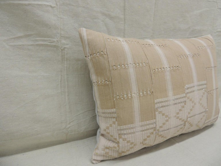 Vintage tan and brown woven ewe stripweaves and white embroidery African long bolster decorative pillow with silver embroidered metallic threads. with textured grey cotton backing. Decorative pillow handcrafted and designed in the USA. Closure