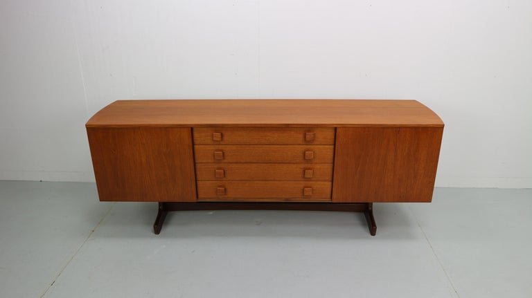 Midcentury sideboard with curves sides in teak wood. Four drawers and 2 doors with shelf's behind it. Refurbished and refinished in hardwax.