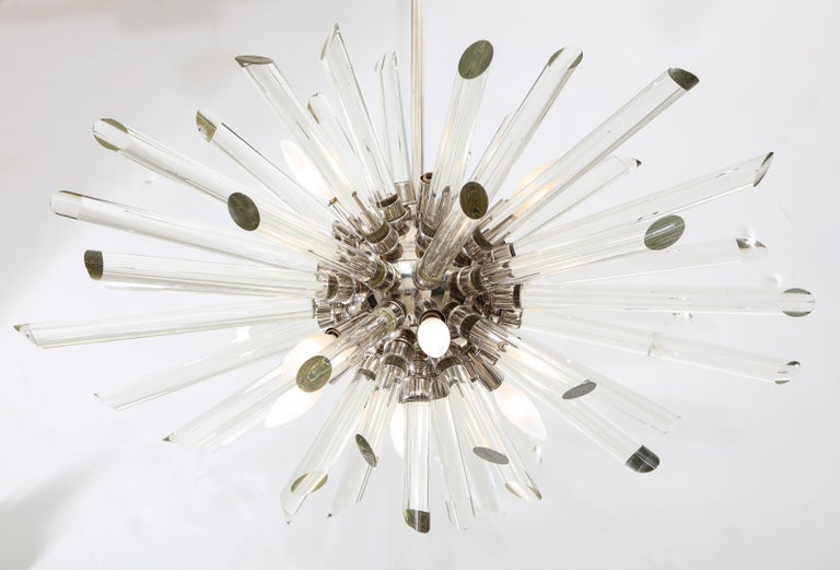 A ten light Sputnik chandelier with numerous glass rods hangs from a nickel-plated central pole that can be adjusted to ceiling height.