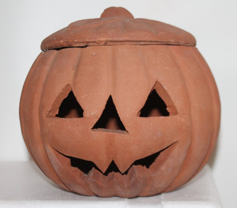 This fun pottery terracotta jack o lantern looks like it was a outdoor porch ornament. Nice wear and worn patina. The inside lip has minor flakes or tiny chips. It is the size of a full size pumpkin.
