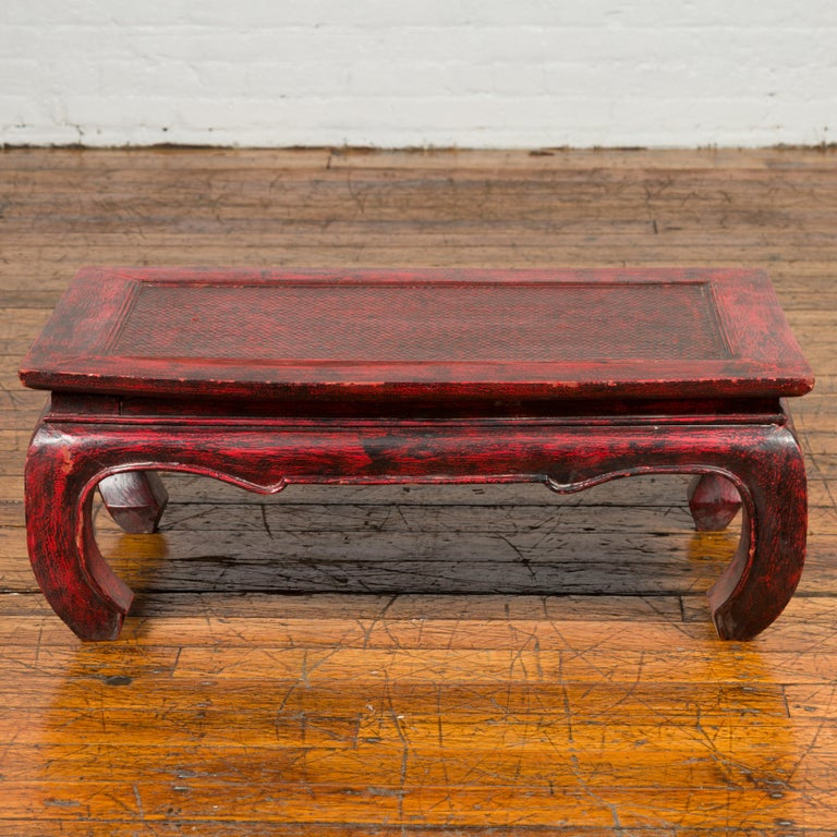 A vintage Thai coffee table from the mid-20th century with red lacquered finish, rattan inset and chow legs. Born in Thailand during the midcentury period, this coffee table features a rectangular top with central rattan inset, sitting above a