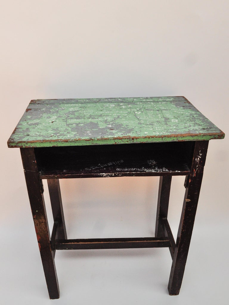 Vintage Thai school desk with painted desktop. North Thailand, mid-20th century. If there are any doubts about the universality of human experience this desktop should lay those to rest. The random notes and drawings that decorate this wonderfully