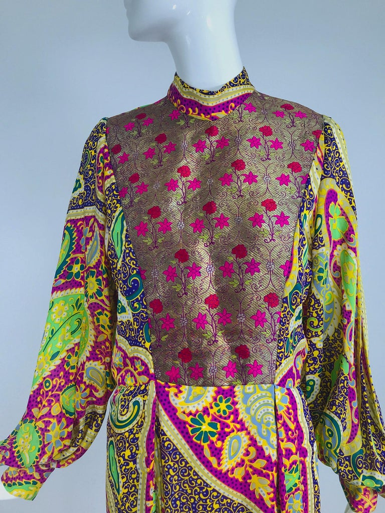 Thea Porter London, paisley silk Print and Brocade Faye Maxi Dress from the 1970s. Bright paisley printed silk dress with long full sleeves, the dress has a band collar, with a front bib of metallic brocade. The Faye dress, named for actress Faye