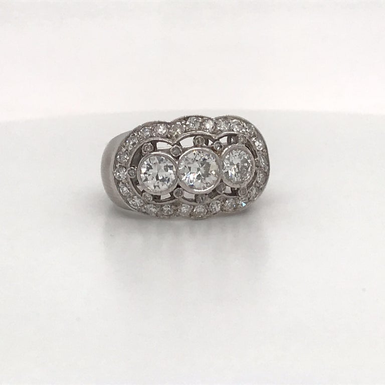 Vintage diamond ring featuring three diamonds flanked with smaller diamonds weighing approximately 2 carats, crafted in platinum.
