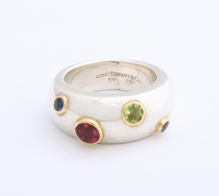 No longer in production, a significant Tiffany wedding or fashion ring sprinkles gold set sapphires, peridot and pink tourmaline in a serpentine river around your finger. The gems are standout with beautiful Tiffany quality with yellow gold bezels