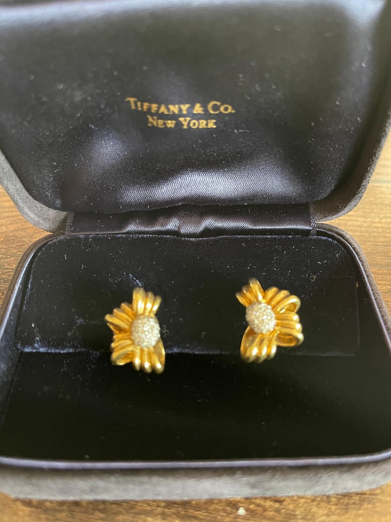 A pretty pair of vintage half bow earrings set with a diamond center by Tiffany & Co. Circa 1980. The center of the earring is pave set with 36 round brilliant diamonds weighing approximately 0.40 carats total. The earrings sit nicely on the ear,