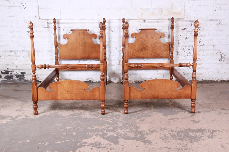 A gorgeous pair of carved tiger maple twin size pineapple poster beds  USA, circa 1950s  Measures: 41.5
