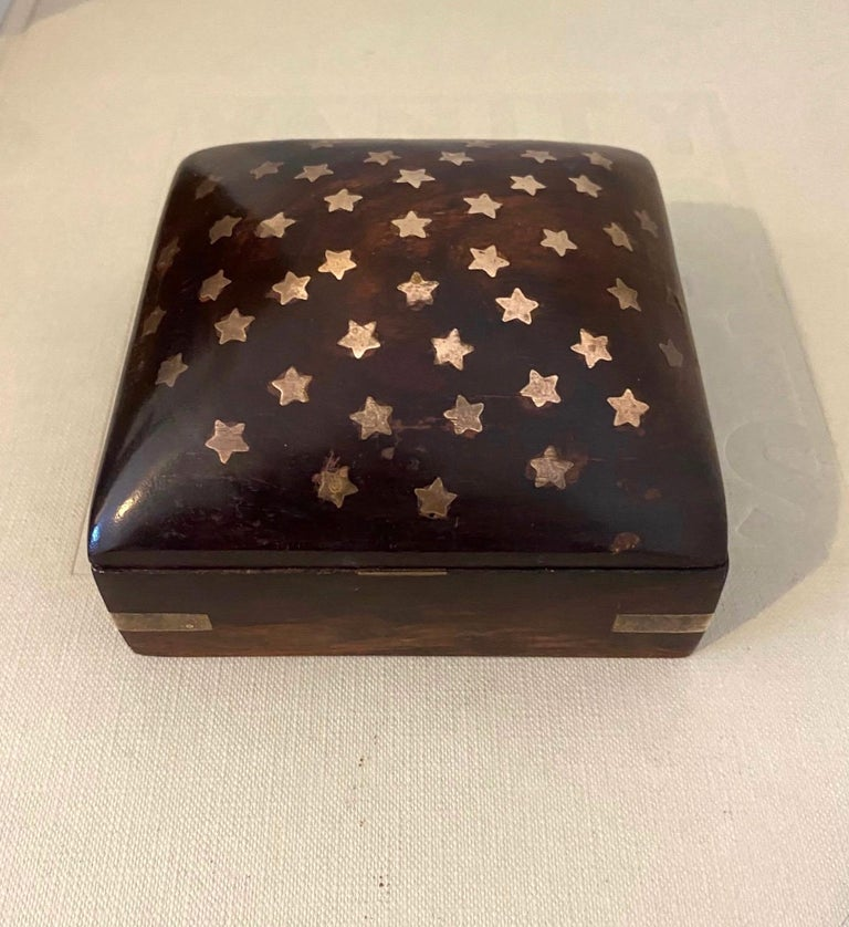 Mid-Century Modern handmade trinket box in rosewood. The box has a square form with a dome top. The lid features beautiful brass star inlays and the corners have brass metal accents. The brass exhibits some patina which only adds to the allure and