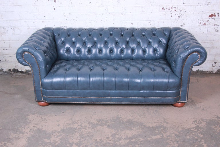 A stunning vintage tufted blue leather Chesterfield sofa. The sofa features gorgeous high grade tufted blue leather with brass nailhead trim. It sits on solid cherrywood bun feet. The sofa is very comfortable and in excellent condition.  The sofa