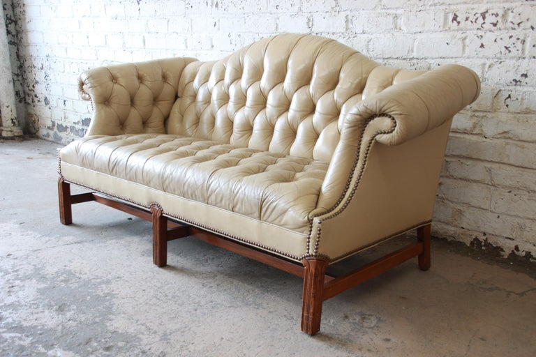 An exceptional vintage tufted tan leather Chesterfield style sofa. The sofa features beautifully aged and distressed tan leather, brass nailhead trim, and scrolled arms. It sits on solid carved walnut legs, with walnut stretchers. Seat height is