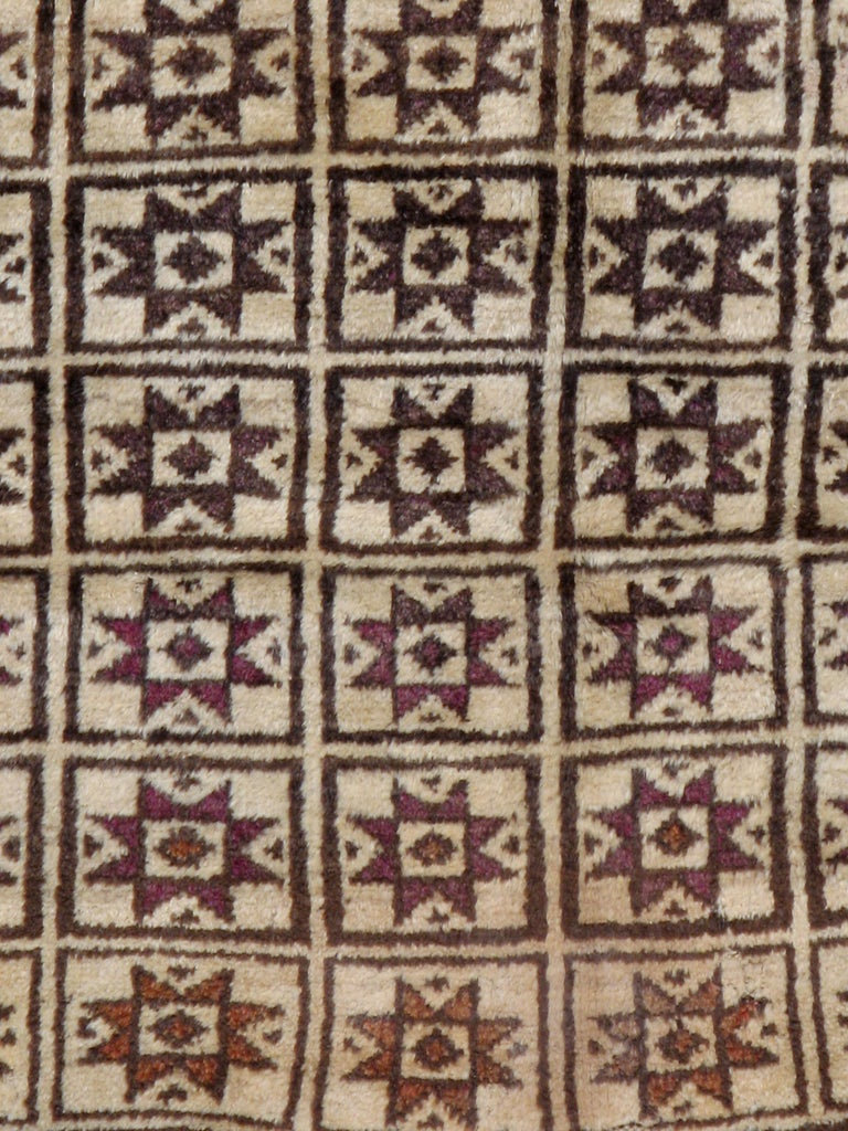 A vintage Turkish Anatolian rug from the mid-20th century. A bichromatic dark brown and sand palette makes an attractive basic scheme for this rustic Turkish scatter with six columns of squares containing eight-pointed stars in shades of aubergine,