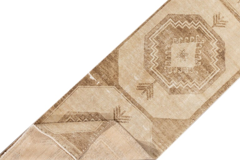 A 20th century vintage Turkish Anatolian runner rug with an all over beige motif. This rug measures at 2'9