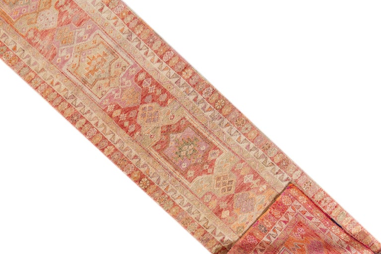 A 20th century vintage Turkish Anatolian runner rug with an all-over pink motif. This rug measures at 2'8