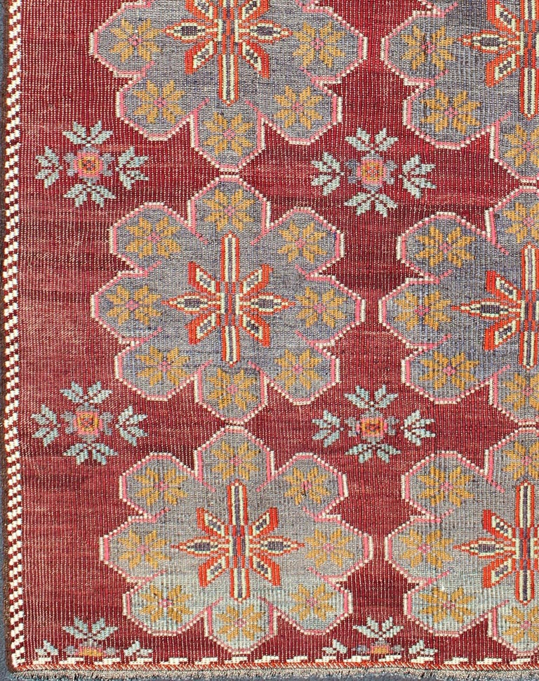 Vintage Turkish Embroidered Kilim Rug in Wine Red, Steel Blue, Pink and Orange. Featuring tribal flowers with a spotted and speckled assortment of geometric elements, this vintage Turkish Kilim showcases an array of rich and colorful tones. Colors